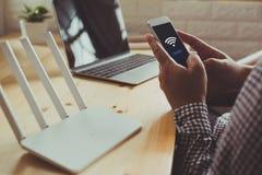Zbliżenie wifi router i mężczyzna używa smartphone na żyć ro obrazy stock