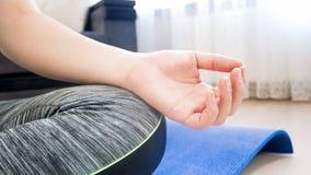 Zbliżenie wizerunek żeński ręki obsiadanie w lotosowym joga positin na podłoga w domu Zdjęcie Stock