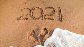 Zbliżenie wizerunek 2021 liczba pisać na piasku na morzu i odciski stopi wyrzucać na brzeg Pojęcie nowy rok, boże narodzenia i po obraz royalty free