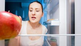 Zbliżenie wizerunek młoda głodna kobieta patrzeje dla coś jeść w chłodziarce przy nocą obrazy stock