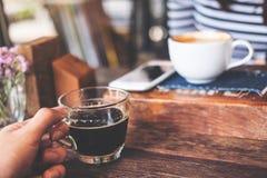 Zbliżenie wizerunek ręka trzyma filiżankę gorąca czarna kawa i herbata na rocznika drewnianym stole w kawiarni z plamy kobietą i  Obrazy Royalty Free