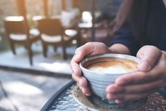Zbliżenie wizerunek ręki trzyma filiżankę gorąca kawa na szkło stole Obraz Stock