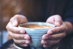 Zbliżenie wizerunek ręki trzyma filiżankę gorąca kawa na szkło stole Zdjęcie Royalty Free