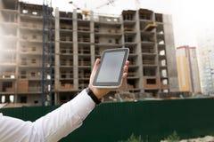 Zbliżenie wizerunek trzyma cyfrową pastylkę z budynkiem męska ręka Fotografia Royalty Free