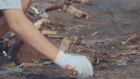 Zbliżenie wolontariuszi siedzi i podnoszący w górę śmieci na plaży Czysty zbieracki śmieci na dennej plaży w czerń zbiory wideo