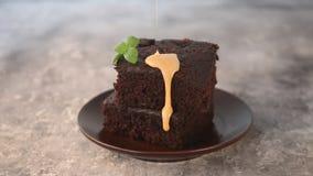 Zbliżenie wyśmienicie czekoladowy karmelu syropu lodowacenia dolewanie od wierzchołka kawałek handmade czekoladowy tort zbiory