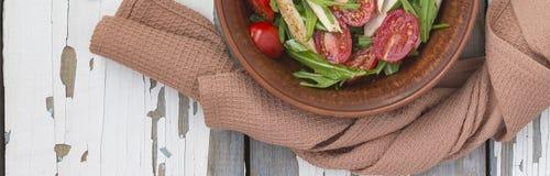 Zbliżenie wyśmienicie sałatka arugula z czereśniowymi pomidorami i kurczak piersią w glinianym pucharze na drewnianym stole, odgó zdjęcie royalty free
