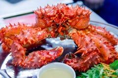 Zbliżenie wyśmienicie smakowity gotujący się świeżo przygotowany czerwony królewiątko krab na metalu naczyniu z cytryną, zielenie obraz royalty free