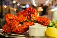 Zbliżenie wyśmienicie smakowity gotujący się świeżo przygotowany czerwony królewiątko krab na metalu naczyniu z cytryną, zielenie fotografia royalty free