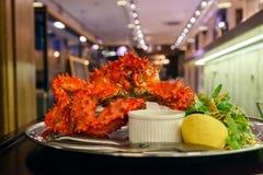 Zbliżenie wyśmienicie smakowity gotujący się świeżo przygotowany czerwony królewiątko krab na metalu naczyniu z cytryną, zielenie obraz stock