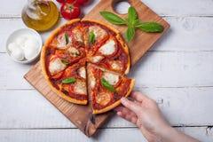 Zbliżenie wyśmienicie Włoska pizza Margherita na białym drewnianym stole Odgórny widok Woman& x27; s ręka bierze kawałek pizza Obraz Royalty Free