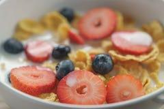 Zbliżenie zdrowy śniadanie z kukurydzanymi płatkami i jagodami w białym pucharze obraz stock