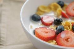 Zbliżenie zdrowy śniadanie z kukurydzanymi płatkami i jagodami w białym pucharze zdjęcie royalty free