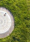 Zbliżenie zielona trawa i manhole fotografia stock