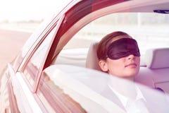 Zbli?enie bizneswomanu drzemanie z mask? w samochodzie fotografia royalty free