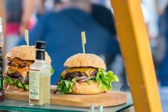 Zbliżenie hamburger na drewnianej desce przy otwartym jedzenie rynkiem w Ljubljana, Slovenia Zdjęcie Stock