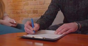 Zbli?enie kr?tkop?d kobieta i m??czyzna robi transakcji na kupowa? nowego mieszkanie Męska ręka podpisuje dokument indoors zdjęcie wideo