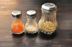 Zbliżenie oregano, pieprzu i chili butelki na w Obrazy Stock