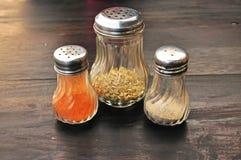 Zbliżenie oregano, pieprzu i chili butelki na w Obraz Stock