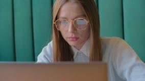 Zbli?enie portret pracuje przy nowo?ytnym biurem i u?ywa komputerowego ekran sensorowego bizneswoman, patrzeje monitoru zbiory