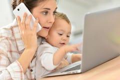 Zbliżenie ruchliwie matka i jej dziecko na laptopie Fotografia Royalty Free
