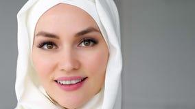 Zbli?enie twarz jest ubranym hijab muzu?ma?ska kobieta jest przygl?daj?cym kamer? i ono u?miecha si? obraz royalty free