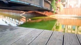 Zbli?enie wizerunek stara drewniana deska lub deski przeciw spokojnej rzece i mostowi w starym europejskim miasteczku kosmos kopi obraz royalty free