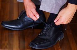 Zbliżenia man& x27; s czerni formalni buty, używa wręczają wiązać koronki, mężczyzna dostaje ubierającego pojęcie Fotografia Royalty Free