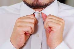 Zbliżenia man& x27; s klatka piersiowa jest ubranym białą koszula, wiąże krawat używać rękę, twarz częsciowo widoczna, mężczyzna  Zdjęcia Royalty Free