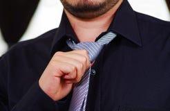 Zbliżenia man& x27; s klatka piersiowa jest ubranym białą koszula, wiąże krawat używać rękę, twarz częsciowo widoczna, mężczyzna  Fotografia Royalty Free