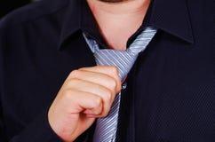 Zbliżenia man& x27; s klatka piersiowa jest ubranym białą koszula, wiąże krawat używać rękę, twarz częsciowo widoczna, mężczyzna  Fotografia Stock