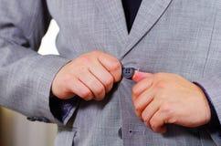 Zbliżenia man& x27; s klatki piersiowej teren jest ubranym formalnego kostium i krawat przystosowywa kurtkę, zapina używać rękę,  Zdjęcie Stock