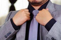 Zbliżenia man& x27; s klatki piersiowej teren jest ubranym formalnego kostium i krawat przystosowywa kurtka kołnierz, używać rękę Fotografia Royalty Free