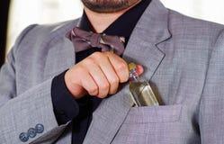 Zbliżenia man& x27; s klatki piersiowej teren jest ubranym formalnego kostium i krawat umieszcza małą trunek butelkę w kurtki kie Zdjęcia Stock