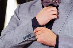 Zbliżenia man& x27; s ręka jest ubranym kostium, przystosowywa cufflinks używać rękę, mężczyzna dostaje ubierającego pojęcie Fotografia Royalty Free