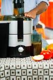 Zbliżenia man& x27; s wręcza używać soku producenta, wkłada marchewki w maszynę z pomarańczowym ciekłym pucharem łączącym, zdrowy Obraz Royalty Free