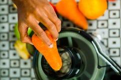 Zbliżenia man& x27; s wręcza używać soku producenta, wkłada marchewki w maszynę, zdrowy stylu życia pojęcie Fotografia Royalty Free