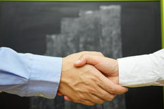 Zbliżenie biznesowy uścisk dłoni z zamazanym wzrostowym wykresem na blac Fotografia Royalty Free