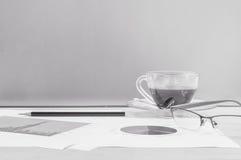 Zbliżenie czarna kawa w filiżance kawy z praca papierem, ołówek i eyeglasses na zamazanym biurku i szklanej ścianie textured tło Obrazy Stock