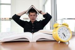 Zbliżenie portret otaczający tonami książki biały człowiek, budzik, stresujący się od projekta ostatecznego terminu, nauka, egzam Obraz Stock