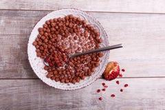 Zboże czekoladowe piłki w pucharze z mlekiem i granatowem obraz stock