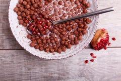 Zboże czekoladowe piłki w pucharze z mlekiem i granatowem obraz royalty free