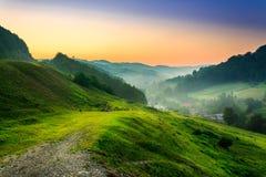 Zbocze blisko wioski w ranek mgle Zdjęcia Royalty Free