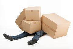 Zbyt ciężcy pudełka. Deliveryman lying on the beach zakrywający z stertą cardb zdjęcie stock