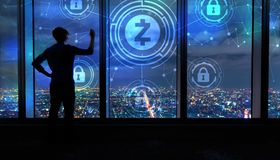 Zcash cryptocurrency security theme with man by large windows at night. Zcash cryptocurrency security theme with man writing on large windows high above a stock images