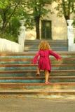 Zdecydowana berbeć dziewczyna w menchiach ubiera dosięgający wierzchołek starzy błękitni roczników schodki fotografia stock