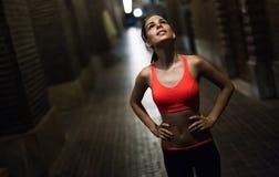 Zdecydowany żeński jogger bieg w mieście przy nocą zdjęcia stock