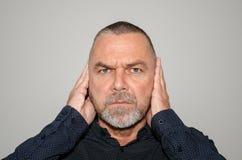 Zdecydowany mężczyzna zakrywa jego ucho z jego rękami zdjęcia stock