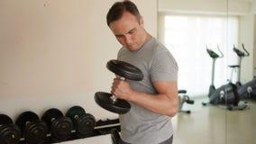 Zdecydowany przystojny dysponowany sportowy młody człowiek w popielatej koszulce robi dumbbell ćwiczy przy gym zbiory
