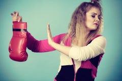 Zdegustowana kobieta trzyma bokserską rękawiczkę zdjęcie stock